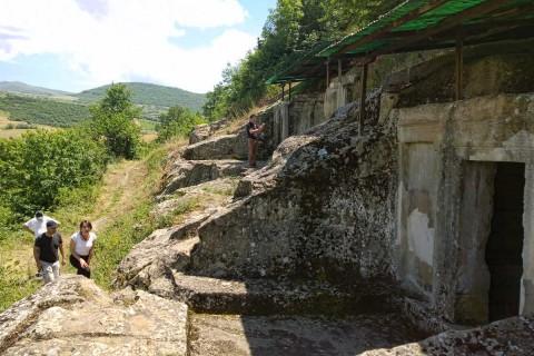 Die frühere Stadt befindet sich auf  einem ringsum freistehenden Berg. Die wuchtigen Reste der Grabfassaden lassen ihre frühere Bedeutung erahnen.