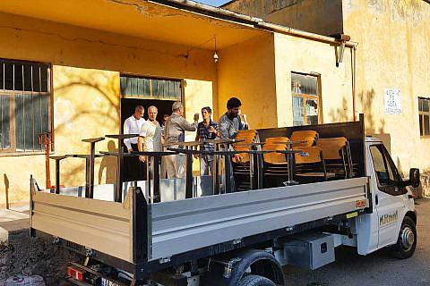 In Diakonia-Lager verladen Helfer gespendete Schulmöbel auf ein Fahrzeug der Stadt Pogradec