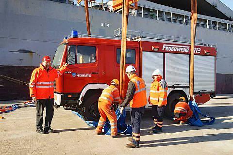 Mitarbeiter von EMS entladen im Hafen von Durrës das Feuerwehrfahrzeug, das während der Seefahrt an Deck vertäut war