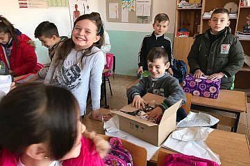 Kinder in der Schule von Zall-Torrë packen fröhlich ihre Weihnachtspäckchen aus